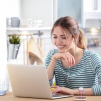 Happy young woman working on laptop at home